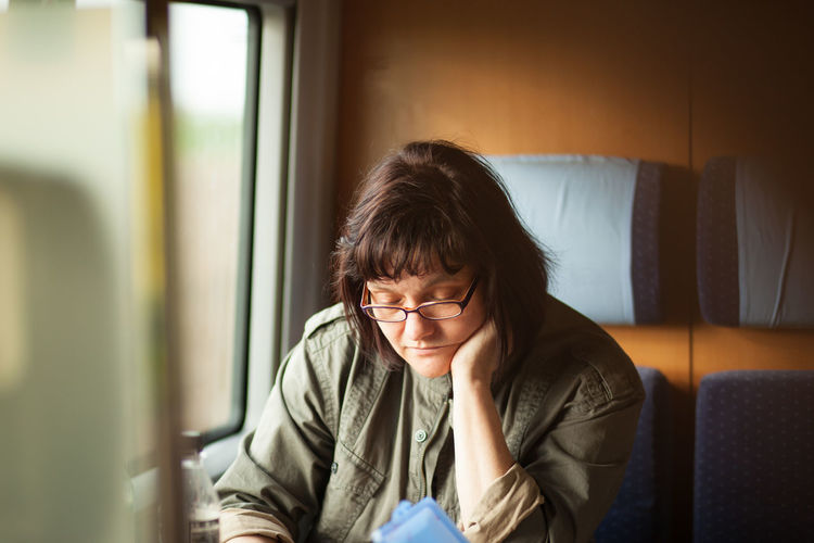Mature woman sitting in train