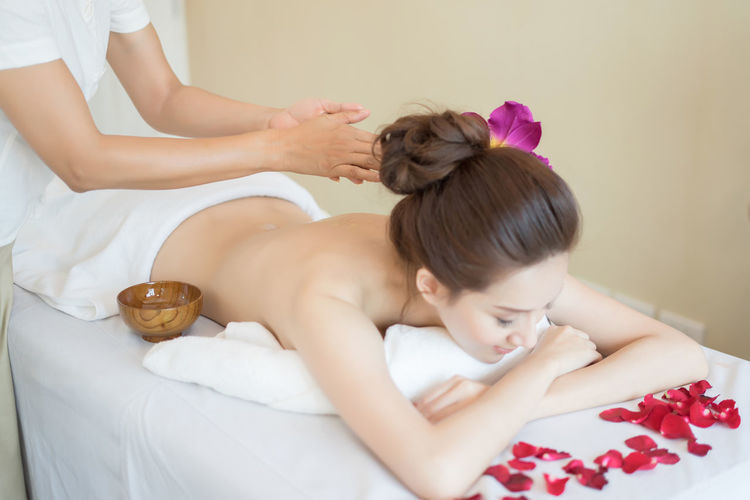 Midsection of masseur massaging young woman with oil in spa