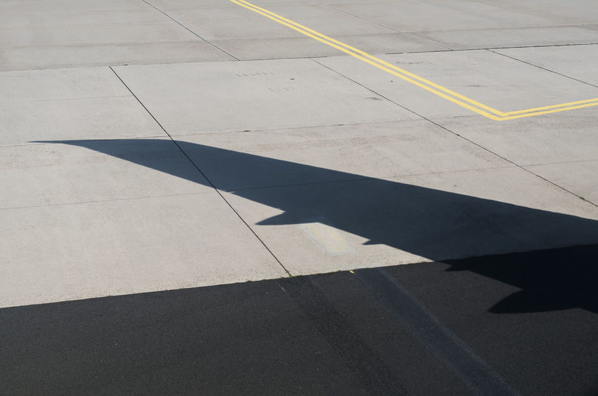 Shadow of the wing of an Airbus A321 on the taxi way. Wing Yellow Line Aircraft Aircraft Wing Airplane Outdoors Shadow Sunlight Taxiway Transportation Wing Shadow
