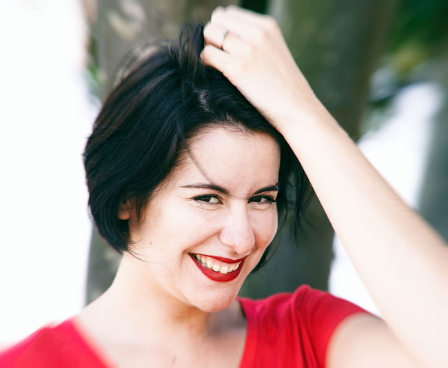 Portrait of smiling woman with hand in hair