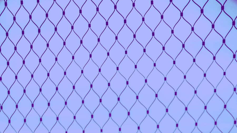Full frame shot of fence against purple background