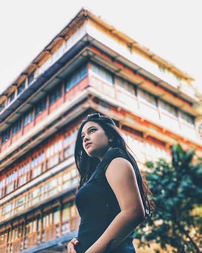 Portrait of beautiful young woman standing against building