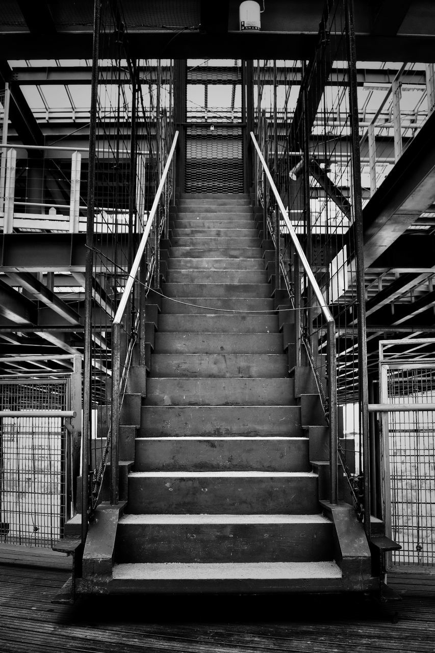 architecture, staircase, railing, built structure, steps and staircases, direction, the way forward, no people, metal, day, low angle view, connection, outdoors, absence, empty, transportation, building, diminishing perspective