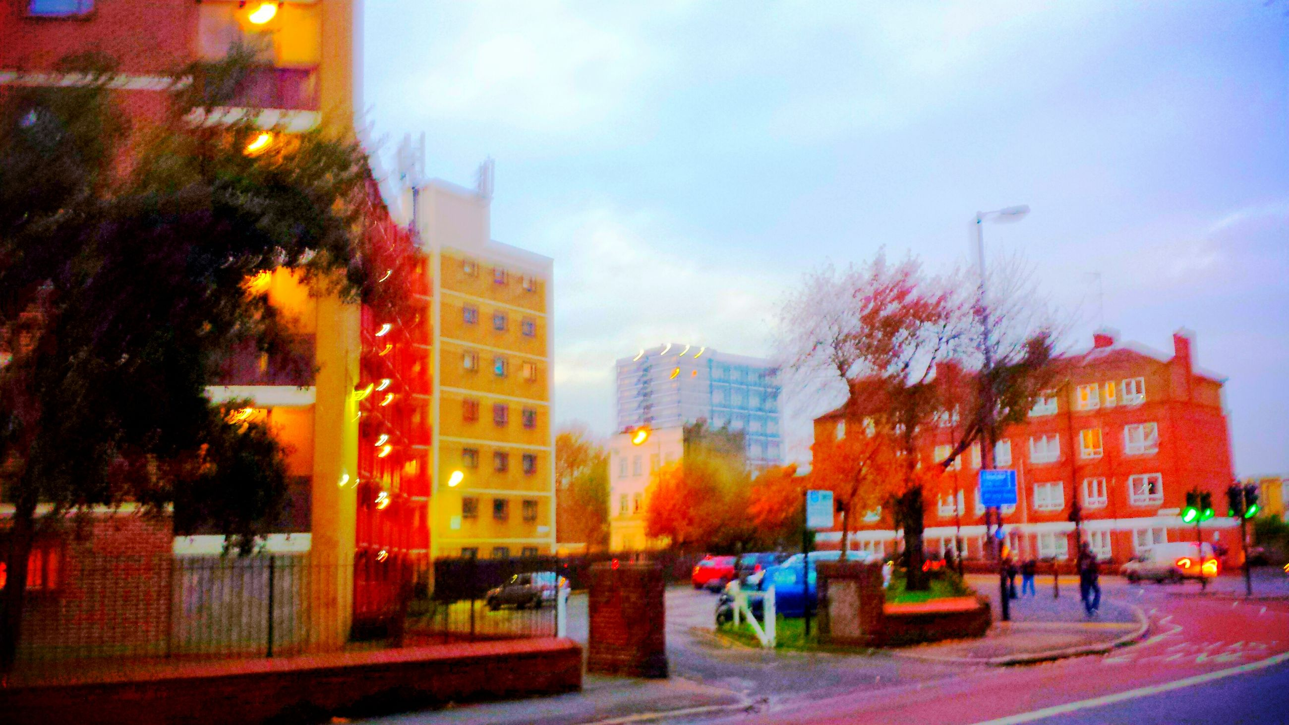 building exterior, architecture, built structure, city, illuminated, sky, street, road, dusk, building, cloud - sky, city life, multi colored, tree, city street, outdoors, residential building, street light, sunset, incidental people