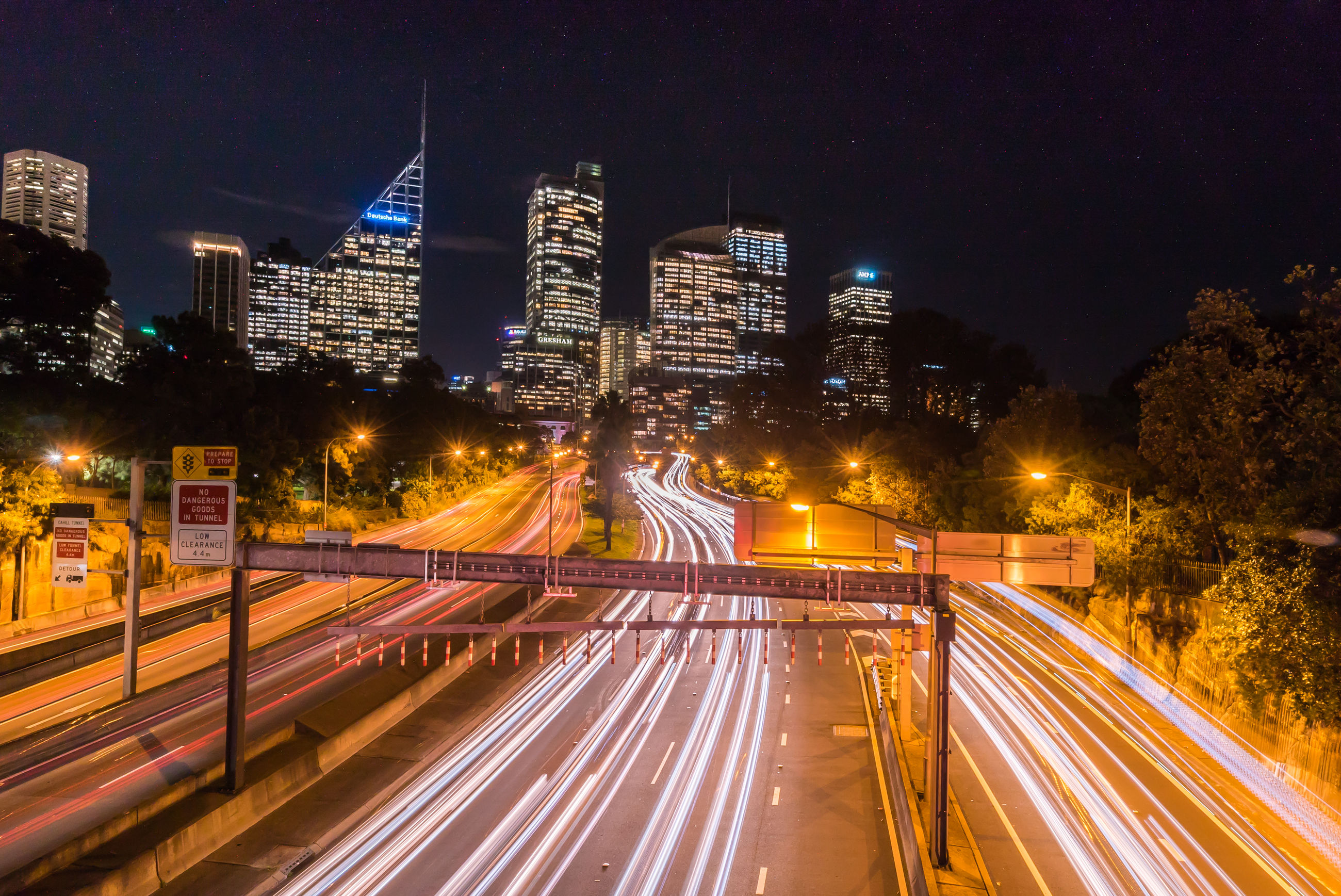 illuminated, night, light trail, long exposure, city, architecture, built structure, speed, building exterior, transportation, motion, high angle view, blurred motion, road, cityscape, city life, street light, sky, skyscraper, modern