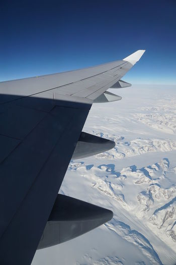 Airplane flying over snowcapped landscape against blue sky