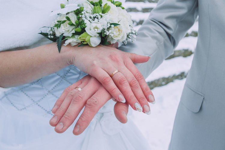 Midsection of groom and bride with bouquet
