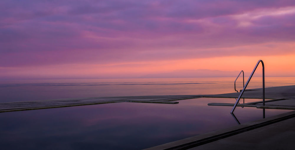 Scenic view of infinity pool against sky during sunset