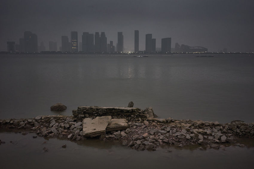 A gloomy and polluted autumn day with view of Hangzhou across the river in the early evening Architecture Building Exterior Built Structure China City Cityscape Darkness Downtown District Fog Hangzhou,China Pollution Reflection River Skyscraper Urban Skyline Water