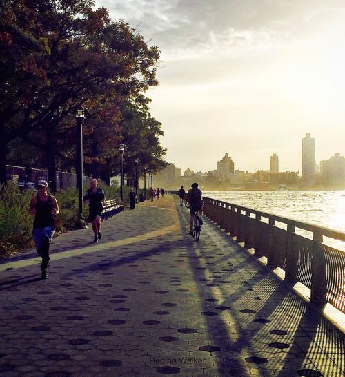 Running and biking Bicycles City City Life Footpath Incidental People New York City Outdoors Perspective Pier Railing Runners Sea Sky Walkway Water