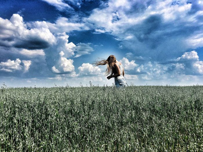 Woman on field against cloudy sky