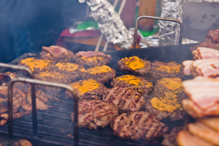 High Angle View Of Meat Cooking On Barbecue Grill At Market