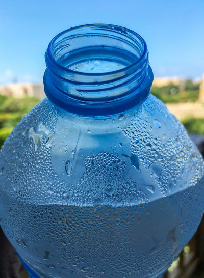 Close-up of wet glass bottle against blue sky
