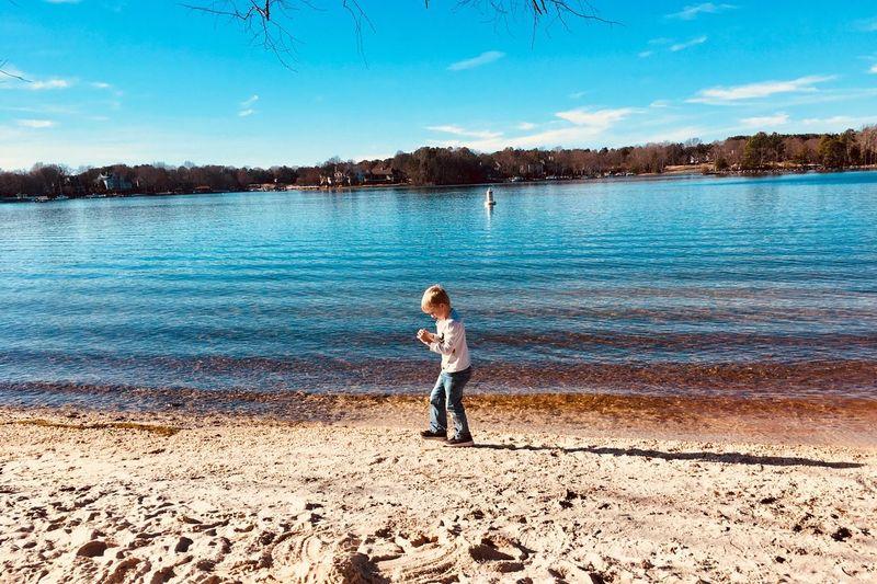 Full length of boy standing at lake against sky