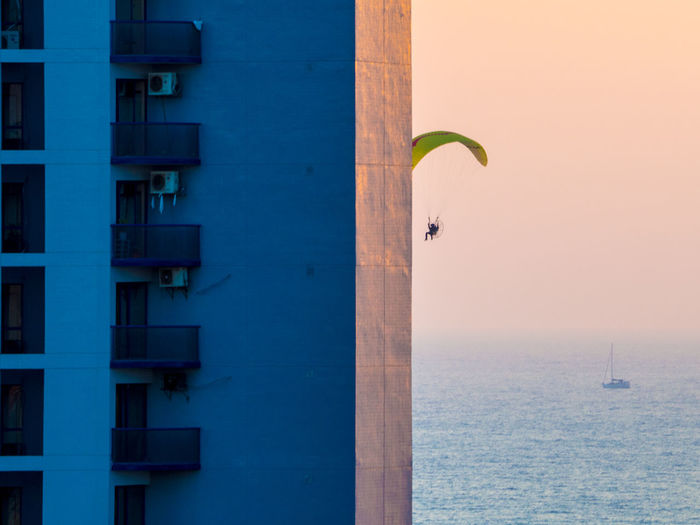 Person paragliding by building against clear sky during sunset