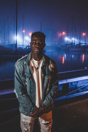 Portrait of young man standing at harbor in night