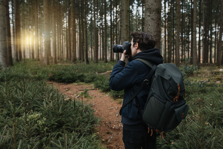 Rear view of man photographing in forest