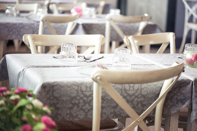 Tables and chairs arranged at shabby chic restaurant