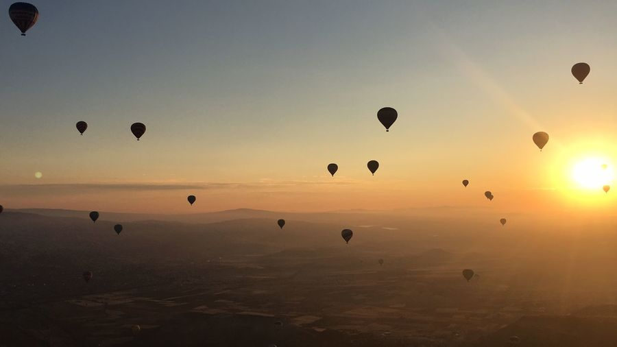 Silhouette hot air balloons flying over landscape during sunrise
