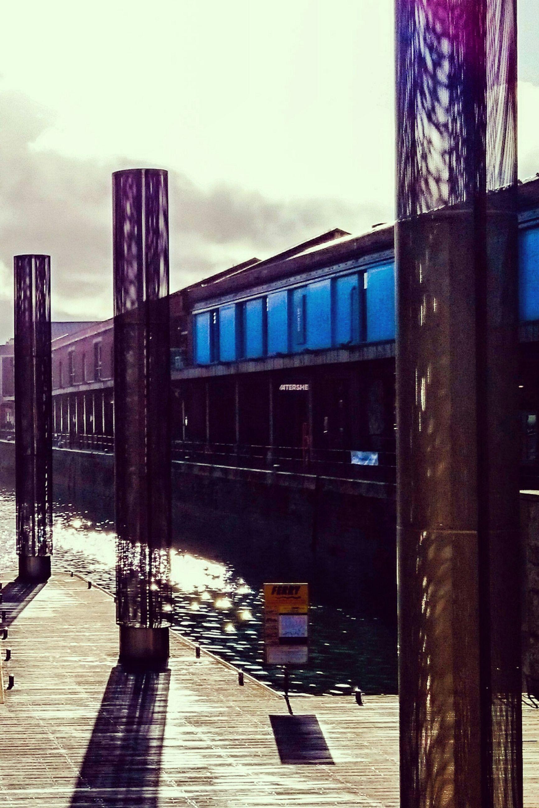 built structure, architecture, railing, building exterior, sky, wood - material, pier, architectural column, empty, column, outdoors, day, absence, boardwalk, bridge - man made structure, no people, footbridge, connection, city, bridge
