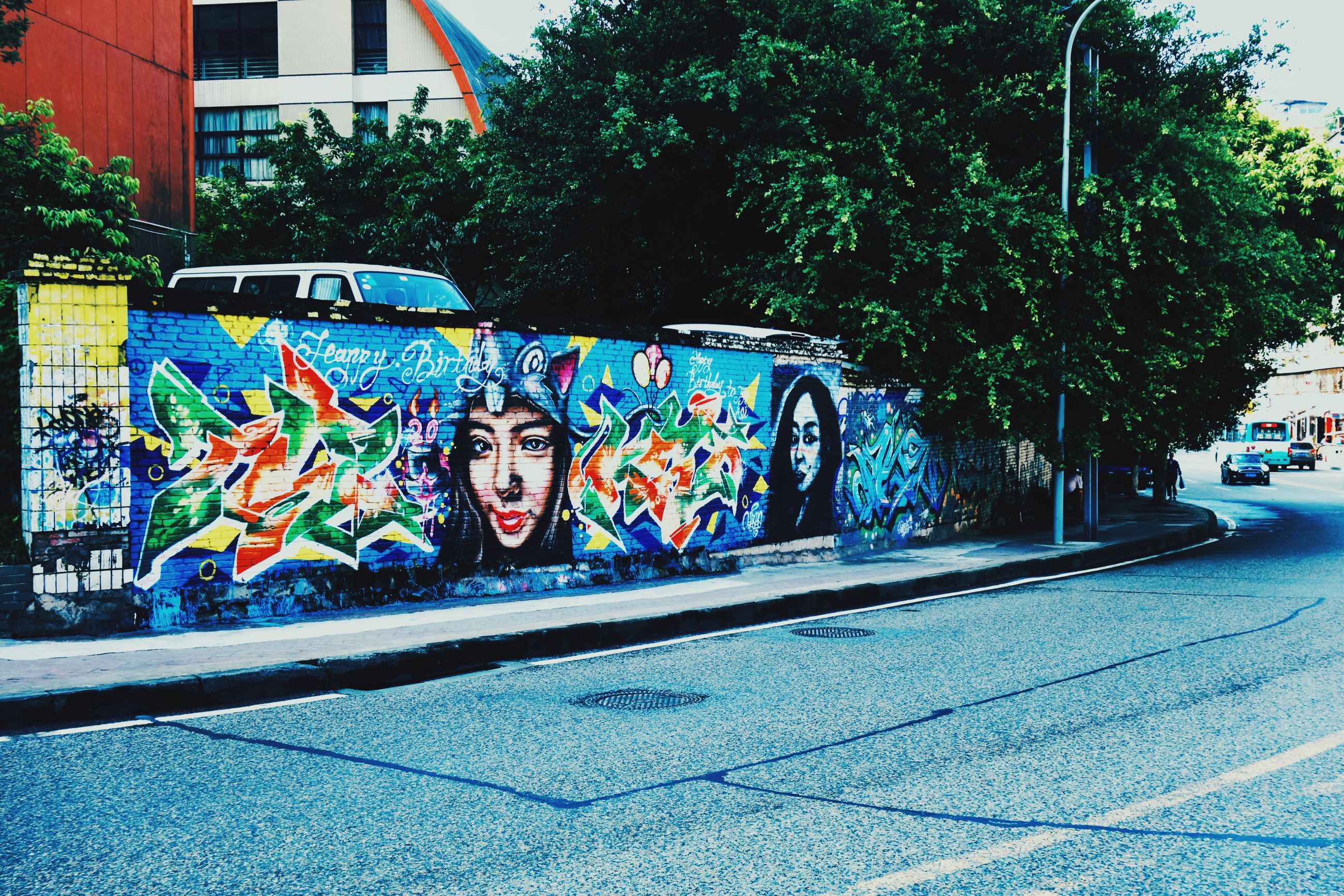graffiti, art, architecture, built structure, art and craft, building exterior, creativity, street, multi colored, text, transportation, street art, city, wall - building feature, road, western script, sidewalk, tree, outdoors, day