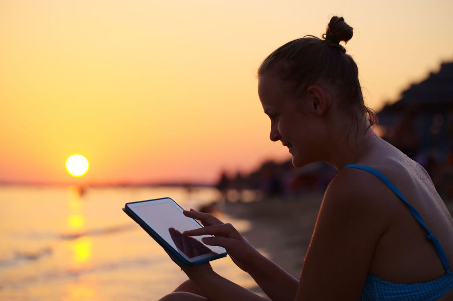 Beach Caucasian Computer Evening Female Girl Girls Horizontal Ocean Outdoor Sea Sun Sunset TAB Tablet Touchpad Touchscreen Vacation Water Woman