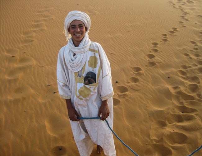 Desert Moroccan Traditional Clothing Day Happiness Looking At Camera Mature Adult Men Moroco Nature One Person Outdoors Portrait Real People Sand Sand Dune Smiling Standing Young Adult