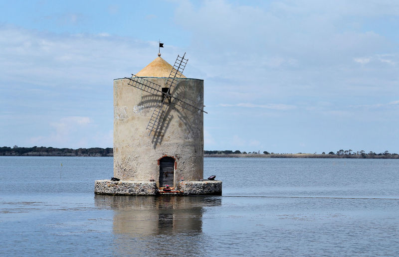 Portrait of the ancient Spanish windmill in the Orbetello lagoon, Tuscany, Italy Water Sky Architecture Built Structure Cloud - Sky Tower No People Travel History Old Building Outdoors Building Exterior Waterfront Sea Lagoon Orbetello Windmill Mill Spanish Italy Cultures Europe EyeEmNewHere EyeEm Best Edits