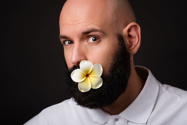Portrait of bald unshaven man with beard and moustache with magnolia flower in mouth on dark background Magnolia Isolated Stylish Bald Man Bearded Man Bearded Man In Coat Black Background Close-up Flower Food And Drink Front View Headshot Hippy Hipster Holding Indoors  Lifestyles Looking At Camera Men Mid Adult One Person Portrait Real People Studio Shot