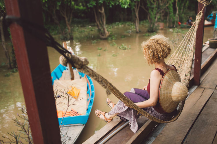 Side View Of Woman Sitting On Hammock Over River
