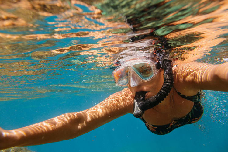 Woman snorkeling. Female diver wearing diving mask swimming in sea. Snorkeling Snorkel Snorkelling Underwater Dive Sea Mast UnderSea Leisure Activity Sport Ocean Summer Holiday Vacation Outdoors Diver Swimming Goggles Gear Face Equipment Recreation  Exploring One Person Woman