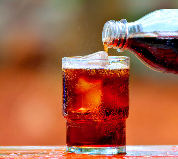 Pouring cola into a glass of ice on blur background. Drink Refreshment Food And Drink Glass Drinking Glass Alcohol Household Equipment Cold Temperature Cola Freshness Close-up Table Glass - Material Bottle Food Focus On Foreground Soda Indoors  Cold Drink Non-alcoholic Beverage Carbonated