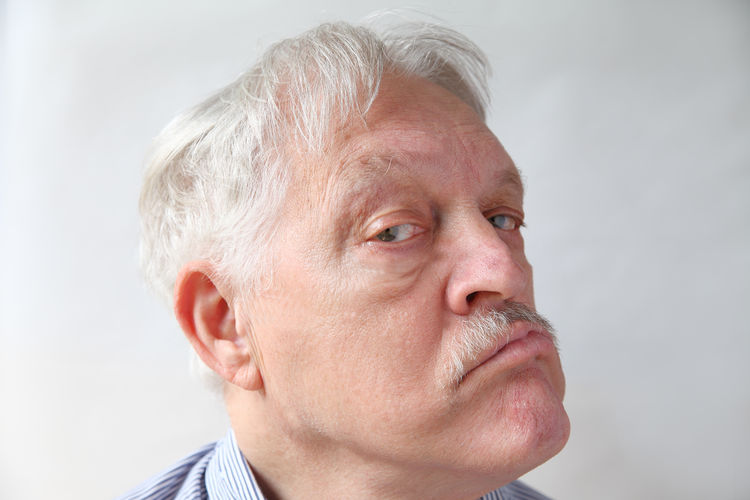 Portrait of man looking away against white background