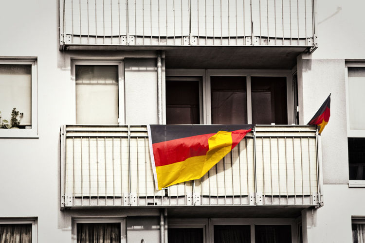 Multi Colored Flags Hanging On Balcony Of Building
