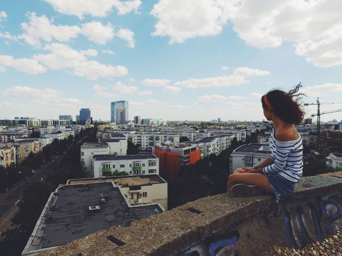 Woman Sitting In City Against Sky