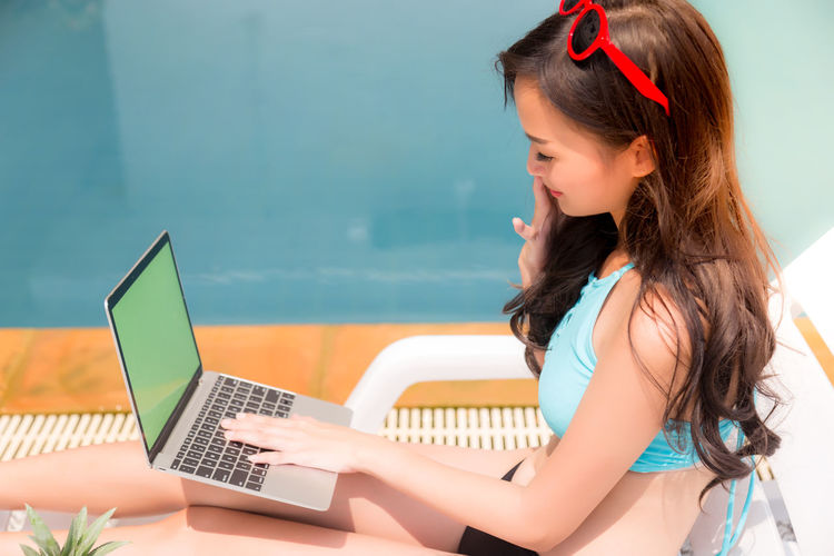 Side View Of Young Woman Using Laptop While Sitting On Chair At Poolside