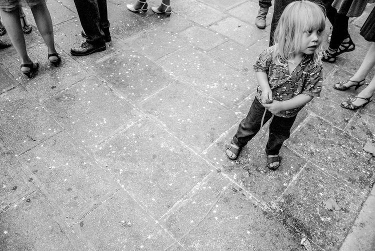 High angle view of girl standing on paved sidewalk