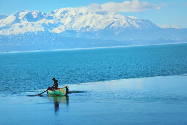 Man on boat in sea against snowcapped mountains