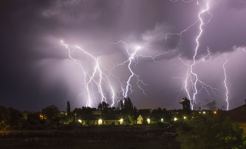 Low angle view of lightning over houses at dusk