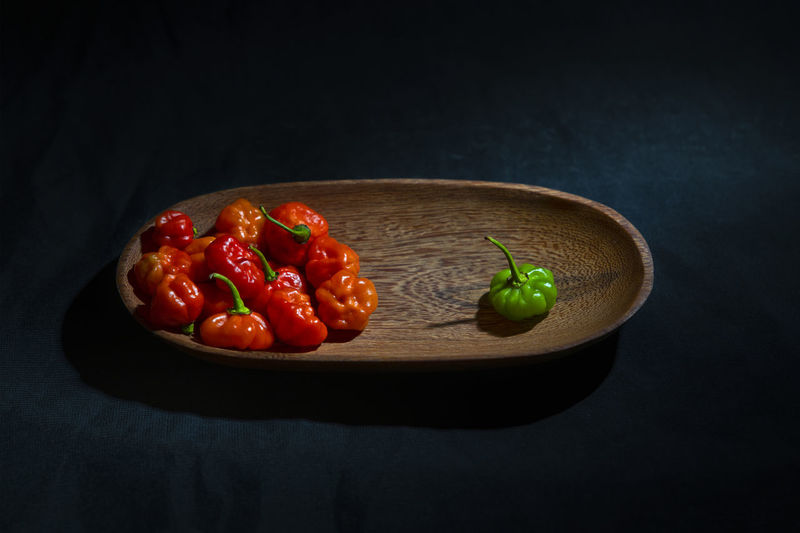 Close-up of fruits and strawberries on table against black background