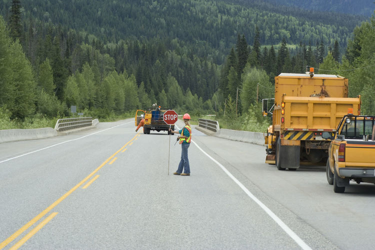 Manual worker with stop sign on road against trees