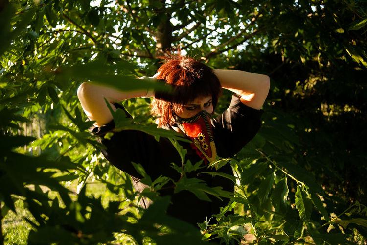 Woman in tree by plants