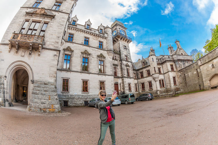Young tourist woman photographer with his smartphone, at Dunrobin fairy Castle, the most northerly of Scotland's great houses of 1300s, Golspie and Brora, Northern Highlands, Scotland, UK. Castle Dunrobin Castle Map Scotland Stirling Tourist United Kingdom Adult Architecture Building Exterior Built Structure Casual Clothing City Cloud - Sky Day Dunrobin Explorer History Lifestyles Monument One Person Outdoors People Real People Sky Standing Uk Woman Portrait Young Adult Young Women