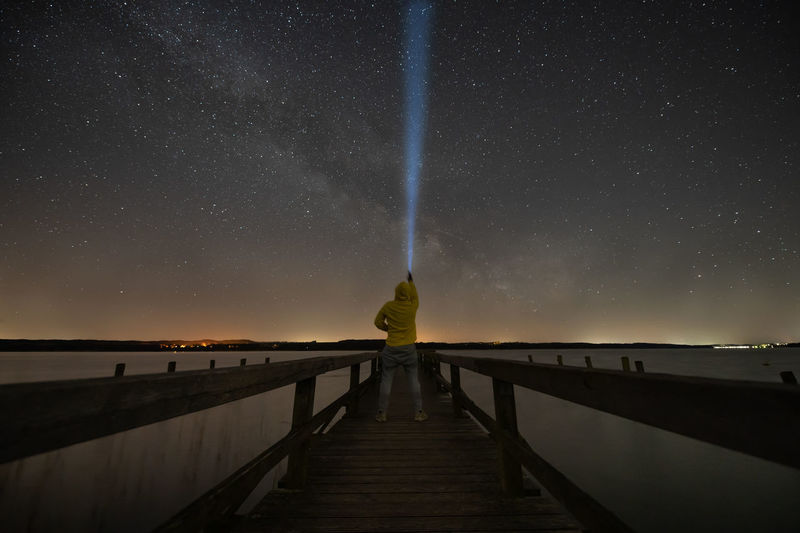 Woman on pier against sky at night