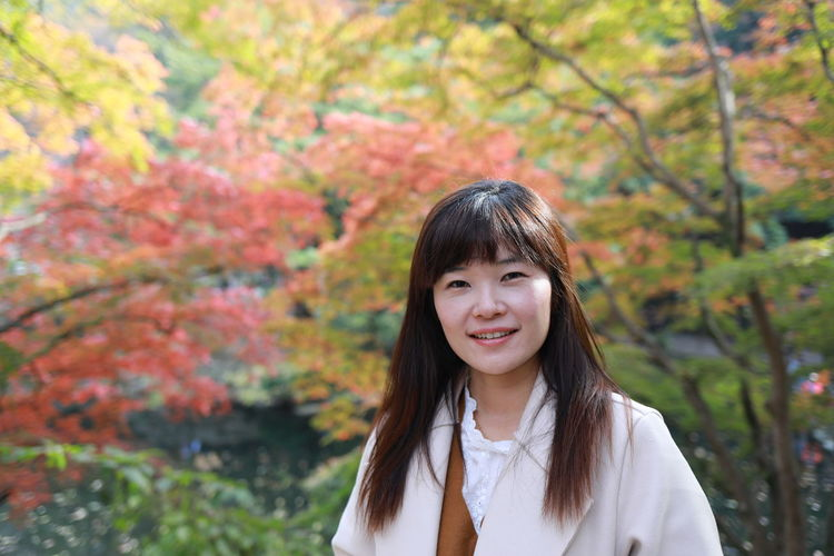 Portrait of smiling woman standing against trees during autumn