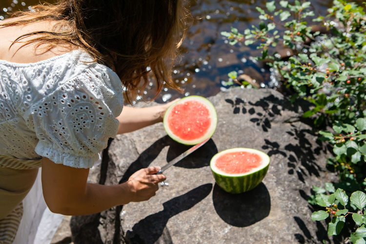 High angle view of woman cutting watermelon by river