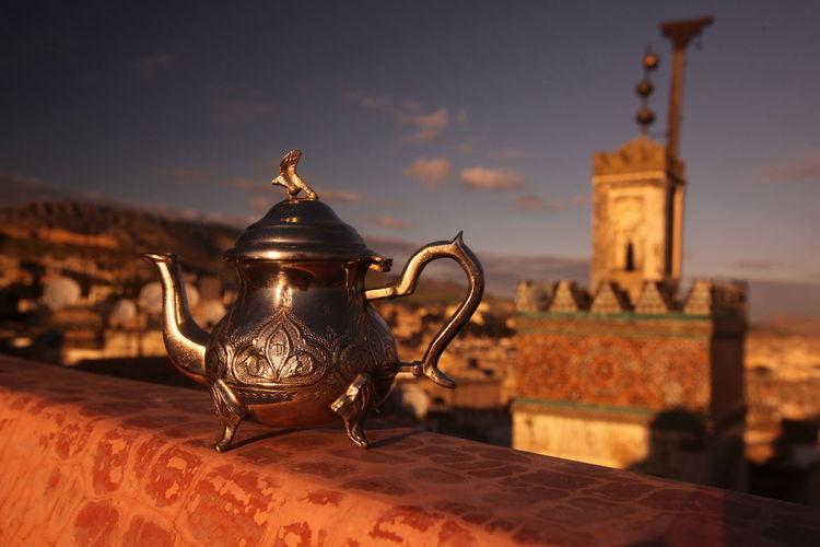 Metallic Teapot On Table Against Town