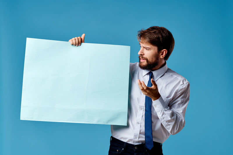 Mid adult man standing against blue background