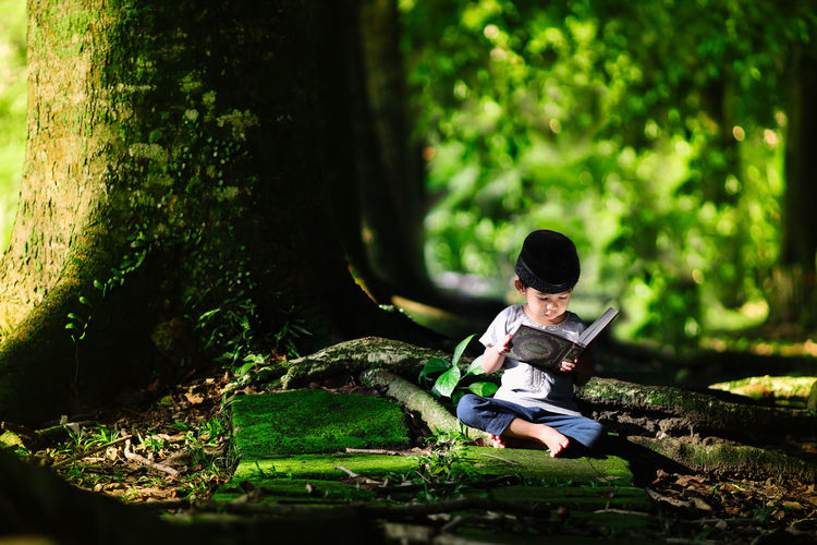 Muslim boy / toddler reciting al Quran at beautiful green nature background with a copy space in Ramadan fasting month Childhood Child Full Length Real People One Person Sitting Boys Men Leisure Activity Males  Plant Day Casual Clothing Nature Tree Innocence Land Outdoors Qoran Quran Muslim Moslem Melayu Malaysia Ramadan  Ramadan Mubarak