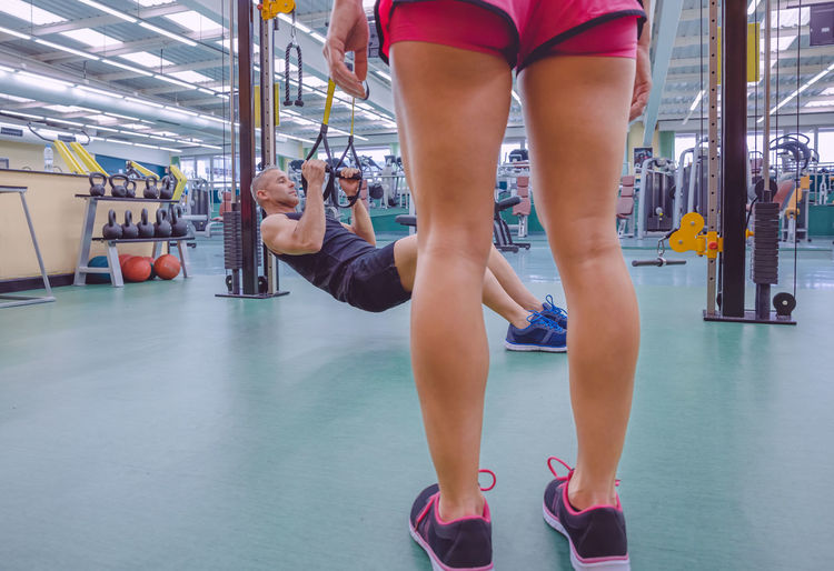 Low section of woman standing while man exercising at gym